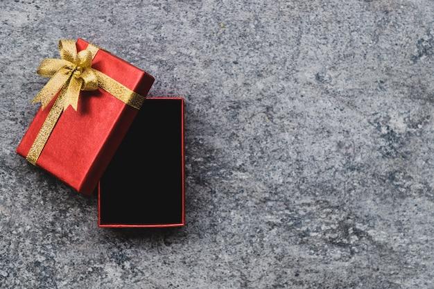 Caja de regalo roja y un lazo dorado que está abierto, colocado sobre una mesa de piedra gris.