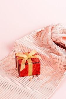 Caja de regalo roja con lazo dorado.
