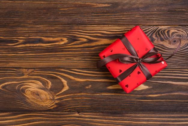 Caja de regalo roja con lazo marrón.