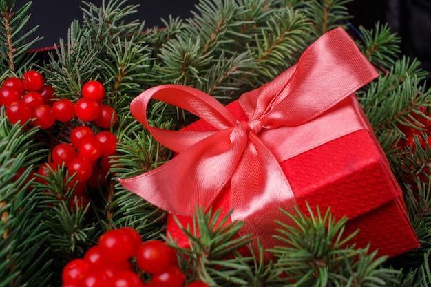 Caja de regalo roja presente con lazo rosa satinado, inmerso en las agujas de un árbol de navidad decorado con bayas rojas.