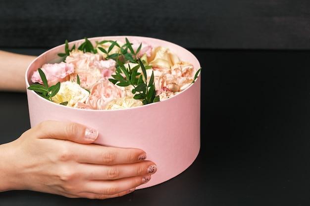 Caja de regalo rosa con una composición floral en manos de mujer sobre fondo negro con espacio de copia. presente para el día de san valentín, día internacional de la mujer, 8 de marzo, día de la madre.