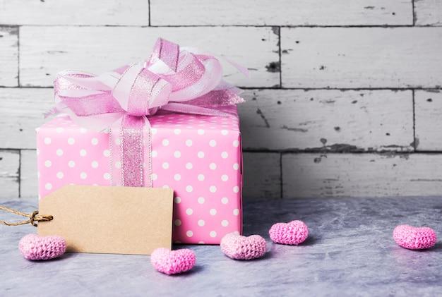 Caja de regalo rosa y etiqueta de papel marrón en blanco con corazón rosa