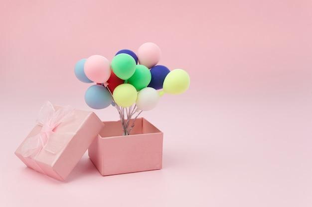 Caja de regalo rosa con globo de colores sobre fondo rosa