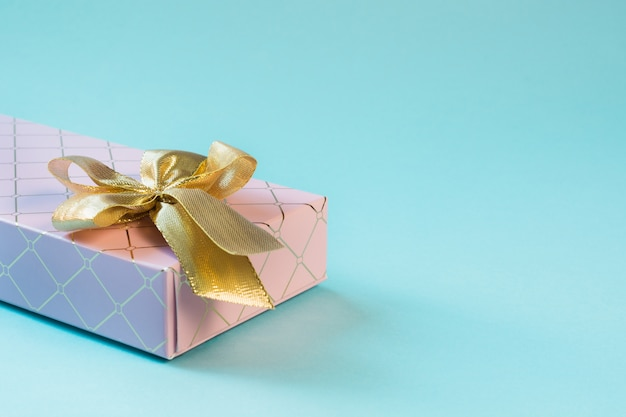 Caja de regalo rosa hembra con cinta dorada en azul pastel. cumpleaños. copyspace