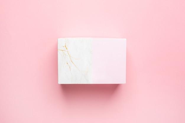 Caja de regalo rosa y mármol aislada en la vista superior de fondo rosa pastel