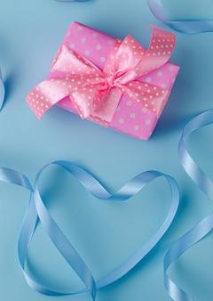 Caja de regalo rosa o presente con cinta sobre fondo azul pastel