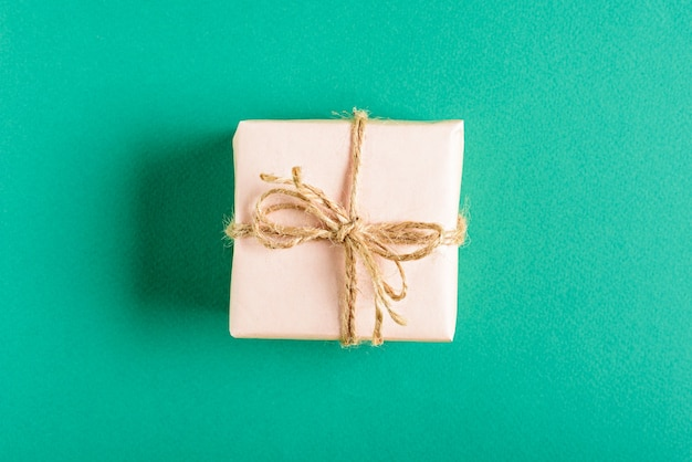 Caja de regalo rosa suave vista superior con lazo sobre fondo verde