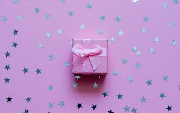 Caja de regalo rosada con las estrellas holográficas en fondo en colores pastel púrpura. telón de fondo festivo vista superior.