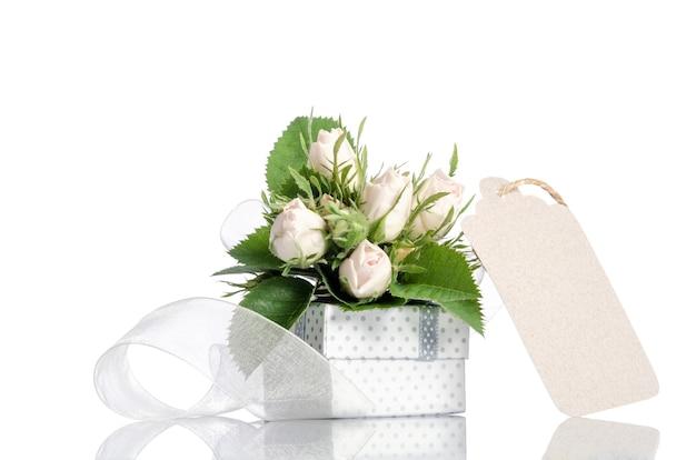Caja de regalo y rosas blancas con etiqueta vacía.