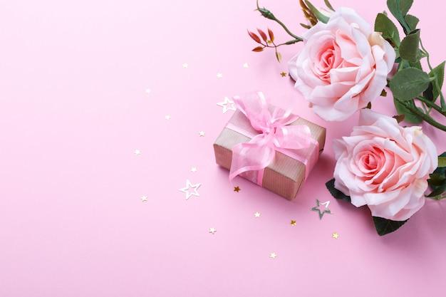 Caja de regalo y rosas rosadas.