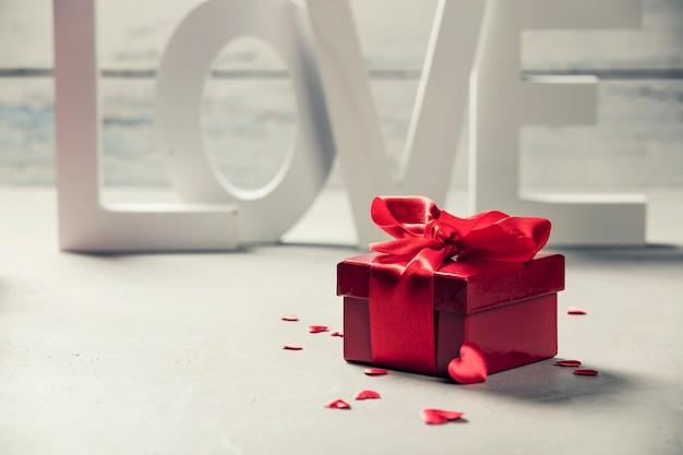 Caja de regalo de san valentín amor letras de madera sobre fondo rústico de madera