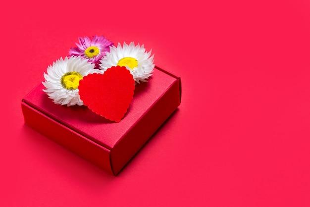 Caja de regalo de san valentín sobre fondo rojo.