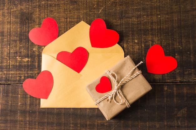 Caja de regalo y sobre con corazones rojos en escritorio