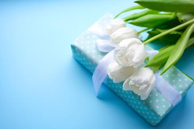 Caja de regalo sobre fondo azul con cinta blanca y flores.