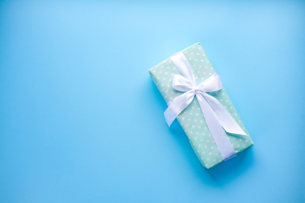Caja de regalo sobre fondo azul con cinta blanca