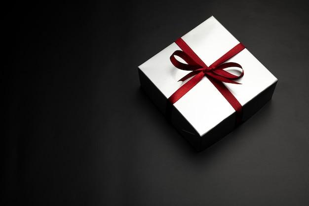 Caja de regalo sobre fondo negro con espacio de copia.