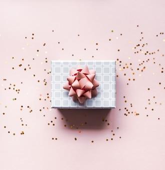 Caja de regalo sobre fondo rosa.
