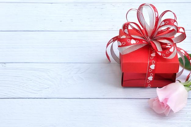 Una caja de regalo y una sola rosa rosa.