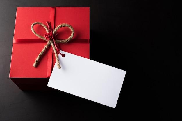 Caja de regalo con tarjeta blanca en blanco.