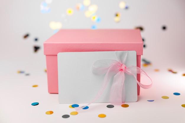 Caja de regalo con tarjeta de regalo o cupón sobre fondo blanco.
