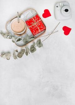 Caja de regalo y taza de bebida en la bandeja cerca de corazones de adorno, ramitas de plantas y cámara