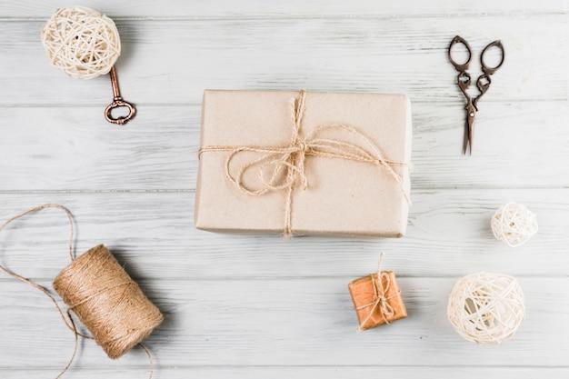 Caja de regalo; tijera de carrete de hilo y bolas decorativas sobre escritorio de madera blanco