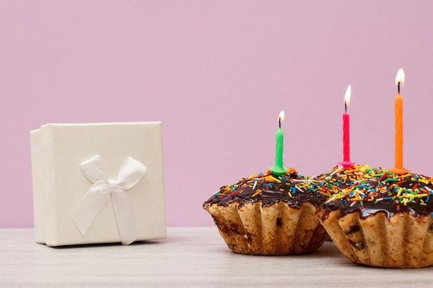 Caja de regalo y tres sabrosos cupcakes de cumpleaños con glaseado de chocolate y caramelo, decorados con velas festivas encendidas sobre fondo lila. feliz cumpleaños concepto mínimo.