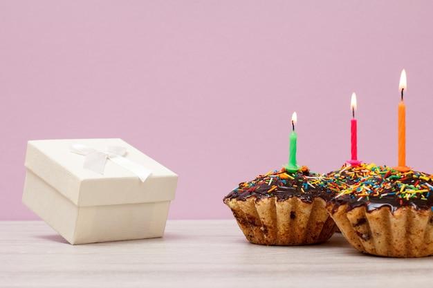 Caja de regalo y tres sabrosos muffins de cumpleaños con glaseado de chocolate y caramelo, decorados con velas festivas encendidas sobre fondo violeta. feliz cumpleaños concepto mínimo.