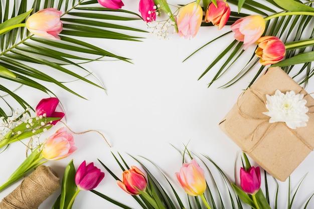 Caja de regalo con tulipanes y palmera.
