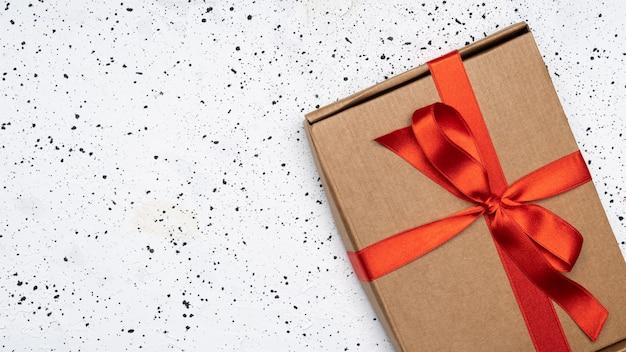 Caja de regalo vintage envuelta con cinta roja sobre fondo de cemento blanco.