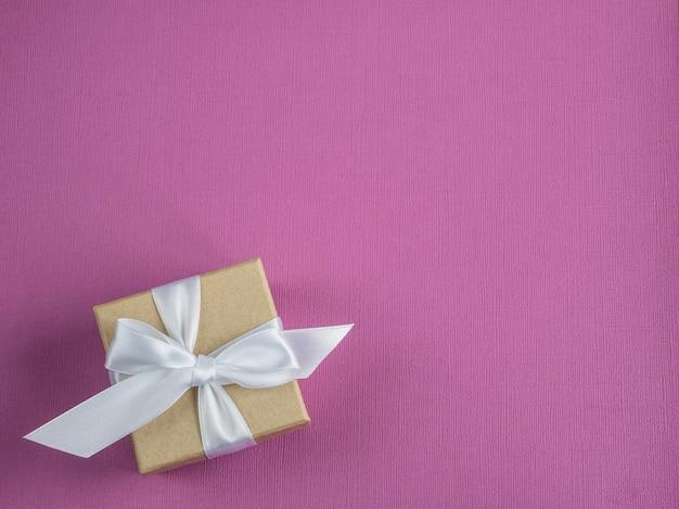 Caja de regalo vintage envuelta. fondo rosa