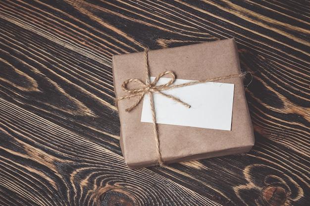 Caja de regalo vintage con etiqueta en blanco sobre fondo de madera vieja.