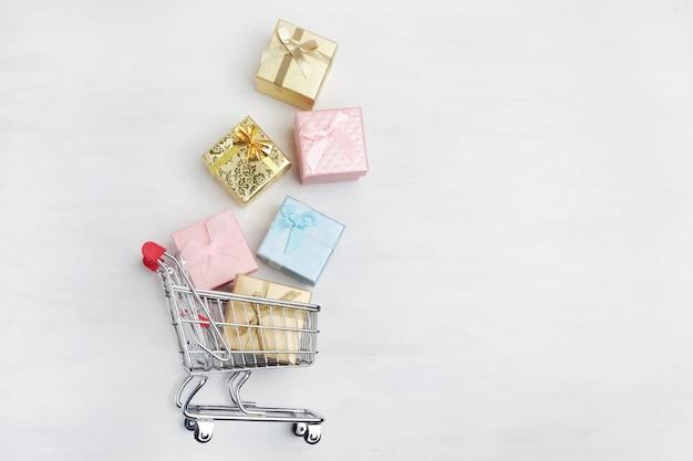Caja de regalos coloridos, carrito de supermercado sobre fondo blanco de madera