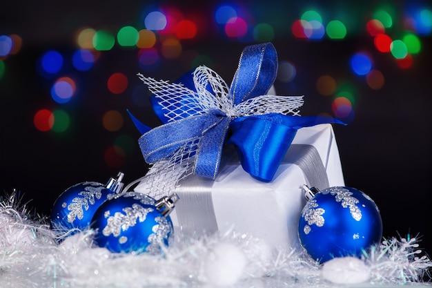 Caja con regalos de navidad sobre un fondo festivo.