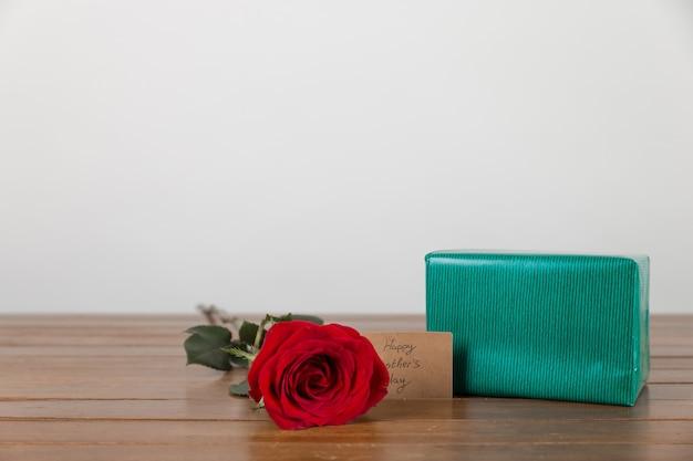 Caja de regalos y rosa con etiqueta