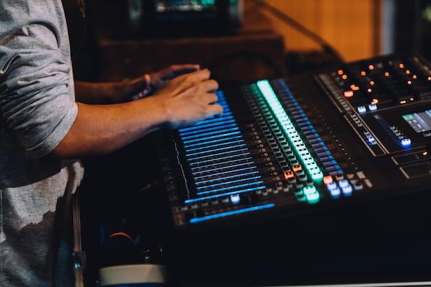 Caja de resonancia profesional que incluye panel de control de mezclador de audio con botones y controles deslizantes.