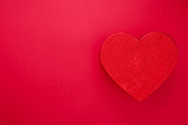 Caja roja brillante en forma de corazón aislada sobre fondo rojo. caja de regalo de san valentín con espacio de copia, maqueta.