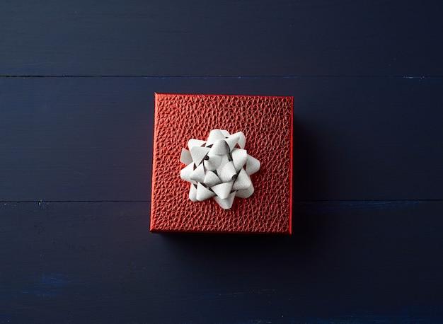 Caja roja cuadrada atada con una cinta dorada, concepto de felicitaciones y regalos