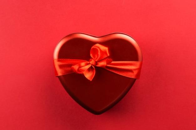 Caja roja en forma de corazón con cinta sobre fondo rojo.