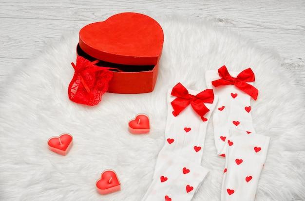 Caja roja en forma de corazón con lencería de encaje, medias blancas con lazos, velas en forma de corazón sobre un pelaje blanco
