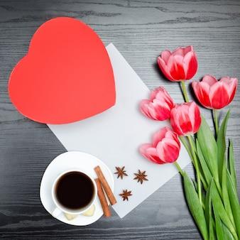 Caja roja en forma de corazón, tulipanes rosados, sábana gris y una taza de café.