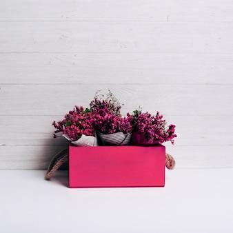 Caja roja con el ramo de flores sobre fondo de madera.