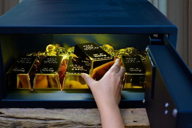 Caja de seguridad de acero electrónica abierta de mano llena de monedas y barra de oro