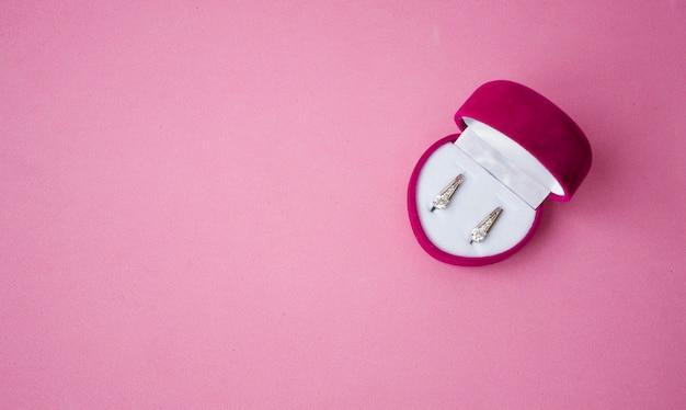 Caja de terciopelo rojo en forma de corazón con pendientes de plata en el interior, un regalo navideño para tu amada