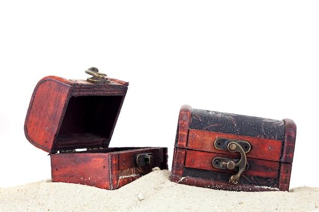 Caja del tesoro en el fondo blanco aislado arena.