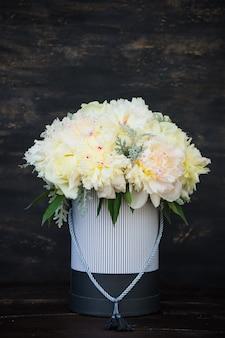 Caja vintage llena de peonías blancas