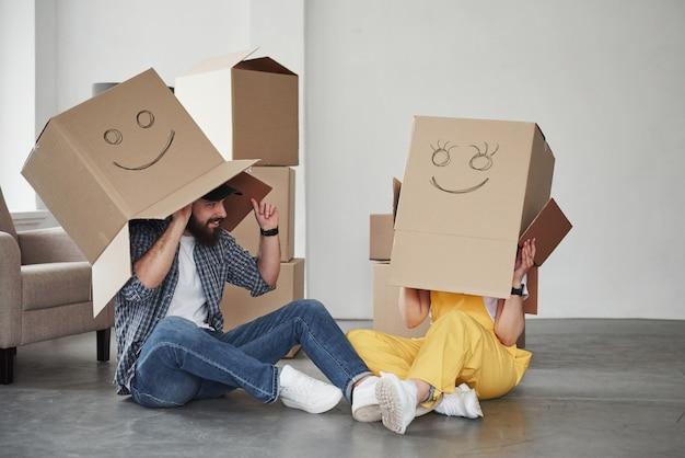 Cajas con caras sonrientes. pareja feliz juntos en su nueva casa. concepción de mudanza