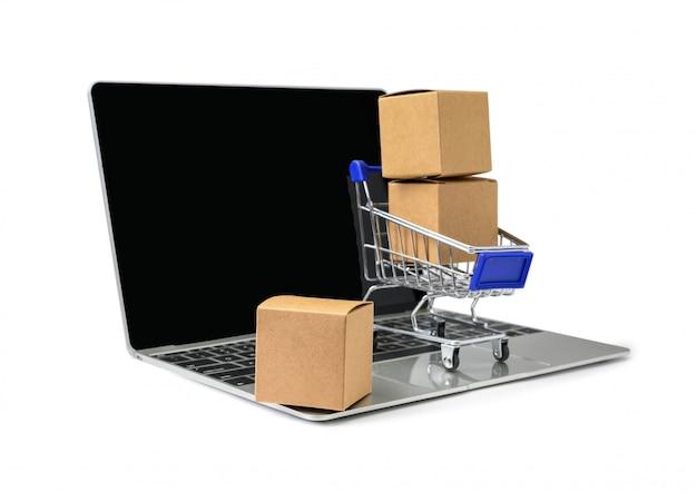 Cajas en una carretilla en un teclado de la computadora portátil en el fondo blanco