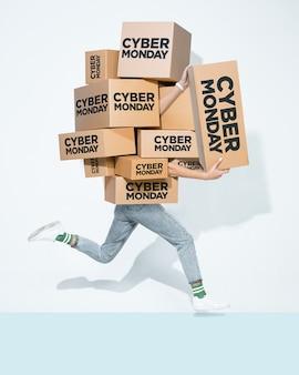 Cajas de cartón con inscripción de cyber monday en manos de un joven