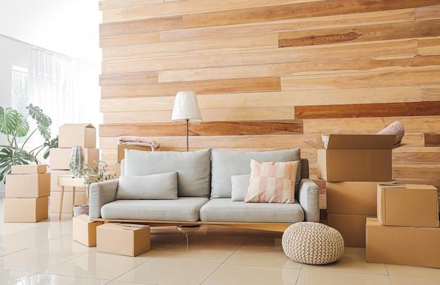 Cajas de cartón con pertenencias y sofá en piso nuevo el día de la mudanza